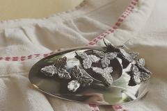 Hopealusikan pesästa valmistettu rintaneula. Koristeet lusikan varsista
